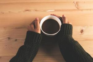 Frauenhände im Pullover, der Tasse Kaffee auf einem hölzernen Tischhintergrund hält