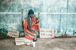 Mann sitzt neben der Straße mit einer obdachlosen Nachricht foto
