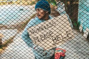 Bettler an einem Zaun mit obdachlosen Nachrichten bitte helfen foto