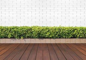 Holzboden mit Pflanzen und weißer Backsteinmauer