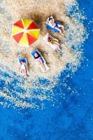 Miniaturfigur Menschen, die sich am Strand sonnen