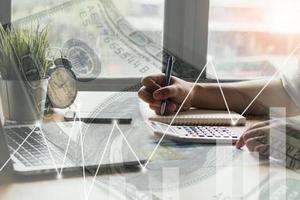 Person, die an einem Schreibtisch mit Geld- und Grafiküberlagerung schreibt foto