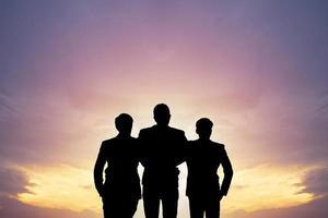 Die Silhouette von drei Personen im Sonnenuntergang
