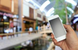 Hand hält Telefon im Einkaufszentrum foto