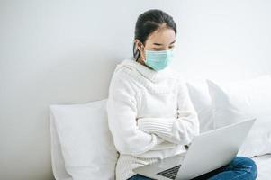 junge Frau, die eine Maske trägt, die auf ihrem Bett sitzt foto