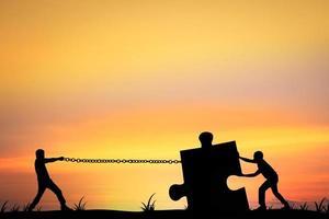 Silhouette von Männern, die helfen, ein Puzzle zu schieben und zu ziehen