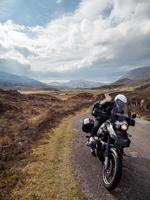 Person auf Motorrad mit Bergen und bewölktem blauem Himmel in Schottland foto