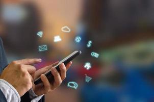 Person, die ein Smartphone mit digitalen Symbolen verwendet foto