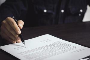 Person, die einen Vertrag unterzeichnet