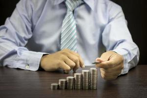 Geschäftsmann, der Münzen stapelt foto