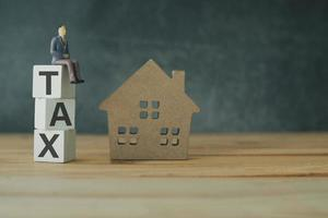 Immobiliensteuer-Management-Konzept, Steuer letztere auf Holz gestapelt mit Hausmodell foto