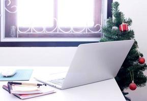 Laptop auf Schreibtisch mit Weihnachtsbaum foto