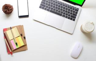 Draufsicht auf Laptop und Telefon mit Büromaterial