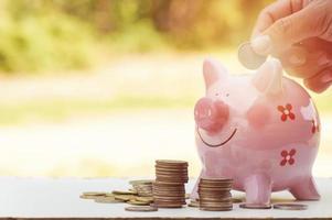 Hand, die Geld in ein rosa Sparschwein legt foto
