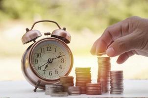Hand legte Geld auf Stapel Münzen mit Uhr foto