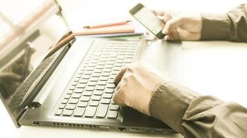 Person, die an Laptop und Telefon arbeitet