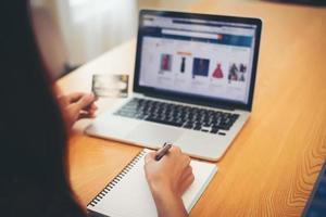 junge Person, die Kreditkarte hält und Laptop verwendet