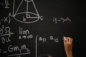 Der Schüler schreibt die Formel mit weißer Kreide an die Tafel foto