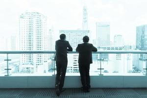 zwei Geschäftsleute, die auf einem Dach sprechen und die Stadt betrachten.