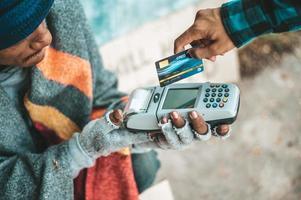 Bettler sitzen unter der Überführung mit einer Kreditkarte und einem Kreditkarten-Swipe-Automaten foto