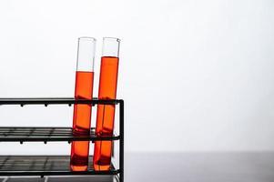 orange Chemikalien in einer Wissenschaftsglasröhre, die auf einem Regal angeordnet ist foto