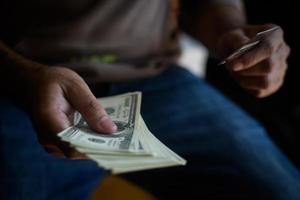 Hände halten Bargeld mit Kreditkarte zum Online-Shopping