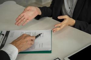 Geschäftsleute, die am Schreibtisch sitzen und auf Dokument für entlassene Unterschrift zeigen foto