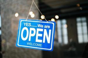 offenes Schild durch das Glasfenster im Café foto