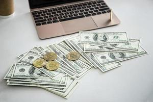 Goldmünzen von Bitcoin auf Dollar-Banknoten foto
