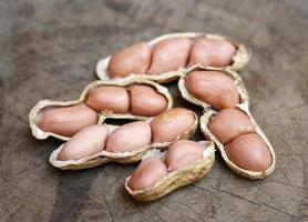 Erdnüsse in Muscheln auf Holz