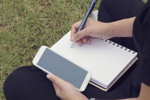 Hand der Frau, die auf Papier schreibt und Telefon benutzt foto