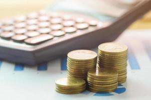 Münzen und Taschenrechner auf Papier Grafik foto