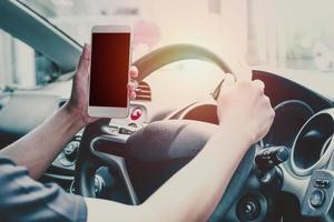Mann im Auto, der auf leerem Bildschirm des Handys schaut foto