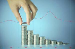 Hand gestapelte Geldmünzen auf blauem Hintergrund foto
