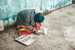Bettler, die mit obdachlosen Nachrichten auf der Straße sitzen, helfen bitte. foto