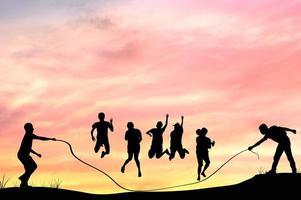 Silhouette von Gruppenleuten Seilspringen foto