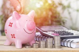 Hand, die Geld auf Rosa des Sparschweins legt foto