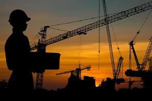 Silhouette des stehenden und haltenden Schutzhelms des Arbeiters foto