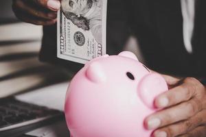 Frau, die Euro-Banknote in ein Sparschwein steckt