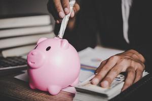 Frau, die Euro-Banknote in ein Sparschwein steckt foto