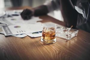 Geschäftsmann, der von Stress am Arbeitsplatz trinkt foto