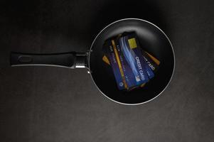 Kreditkarten in einer Pfanne auf einem schwarzen Hintergrund