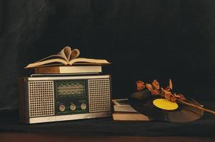 herzförmige Bücher auf Retro-Radioempfänger mit getrockneten Blumen und alter Schallplatte foto