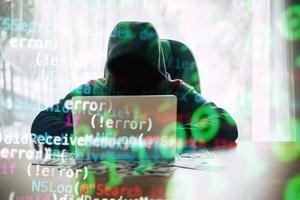 Hacker vor seinem Computer mit Dollar-Banknoten foto