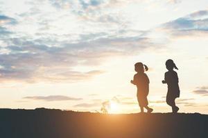 Sonnenuntergangssilhouette der spielenden Kinder foto