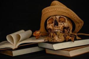 Stillleben mit einem herzförmigen Buch und einem Schädel mit trockenen Blumen