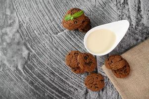 Kekse und ein Löffel Milch auf einem Tuch