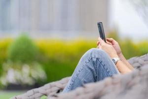 Mann, der sich entspannt und Smartphone in einem Stadtpark benutzt foto