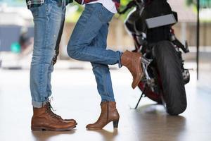 Paar küsst in der Nähe von Motorrad foto