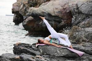 eine schlanke und gesunde Frau, die Yoga auf einem Felsen an einer Seeküste praktiziert